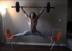 This crazy guy does the splits on two chairs while lifting 100lbs